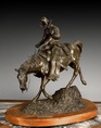 A CAST BRONZE COWBOY STATUE WITH THE TITLE