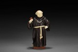 A WESTERN IRONWOOD AND IVORY MONK FIGURE