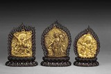 A SET OF THREE GILT BRONZE BUDDHA INSETS WITH ZITAN WOOD STANDS