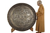 A RARE AND LARGE TIBETAN CARVED SILVER AND GILT MANDALA