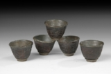 A SET OF FIVE CARVED COCONUT CUPS