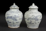 A PAIR OF BLUE AND WHITE 'CRANES' SMALL JARS WITH COVERS