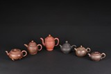 A SET OF SIX ZISHA TEAPOTS