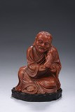 A CARVED SHOUSHAN SEATED 'TAMING LION' LUOHAN