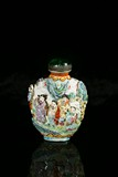 A FAMILLE ROSE MOULDED 'EIGHT IMMORTALS' SNUFF BOTTLE
