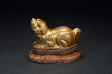 A GILT BRONZE MODEL OF MYTHICAL BEAST WITH STAND