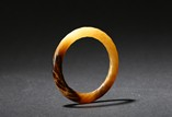 AN ARCHAIC MOTTLED JADE TWISTED-ROPE BANGLE