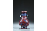 AN IRON RED GROUND BLUE AND WHITE 'DRAGON PHOENIX' VASE