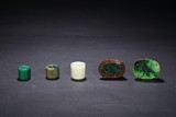 A GROUP OF FIVE JADEITE RINGS AND BUCKLES
