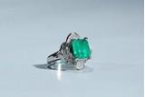 AN EMERALD AND DIAMOND WHITE GOLD RING