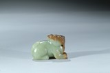 A CELADON AND RUSSET JADE CARVING OF MYTHICAL BEAST