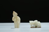 A GROUP OF TWO WHITE AND RUSSET JADE CARVED BOY FIGURES
