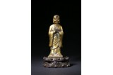 A CHINESE GILT BRONZE FIGURE OF STANDING ANANDA