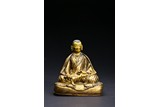 A CARVED GILT-BRONZE FIGURE OF LAMA