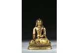 A GILT BRONZE FIGURE OF SEATED SHAKYAMUNI