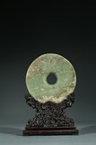 A CHINESE CELADON JADE DISC WITH HARDWOOD STAND