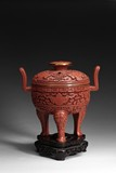 A CARVED CINNABAR LACQUER 'TAOTIE' TRIPOD CENSER AND COVER