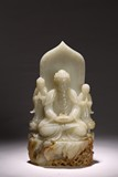 A WHITE JADE CARVED BUDDHA AND ATTENDANTS