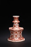 AN IRON RED ENAMEL CANDLESTICK