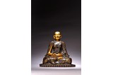 A ZITAN CARVED GILT INSCRIBED FIGURE OF SEATED GURU